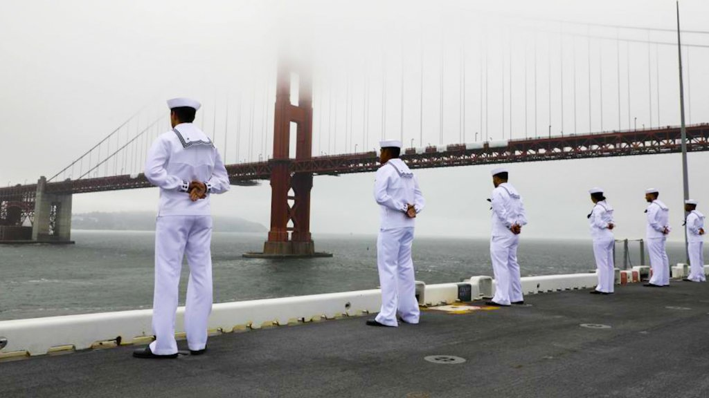 Sailors in white uniforms stand at the edge of the ship's deck as the ship sails under the Golden Gate Bridge