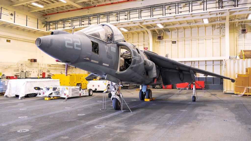 An engineless fighter plane sits in the hangar of a ship