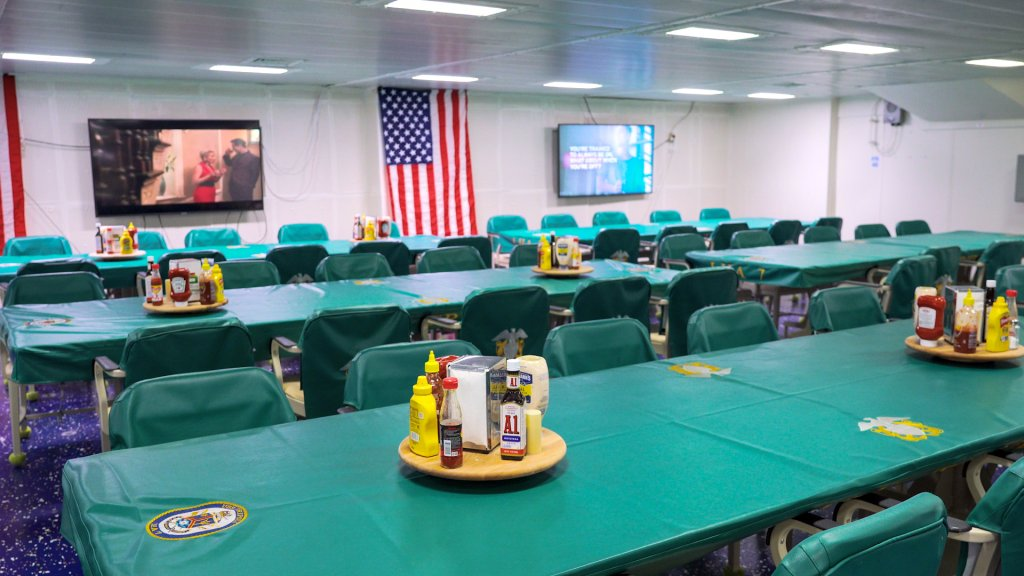 Tables and chairs with condiment shelves covered in green fabric.  An American flag and television screens hang on the wall in the background.