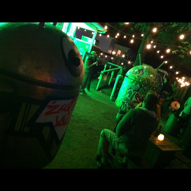 Droid statues hang out with patrons of the Google Village at SXSW 2012.
