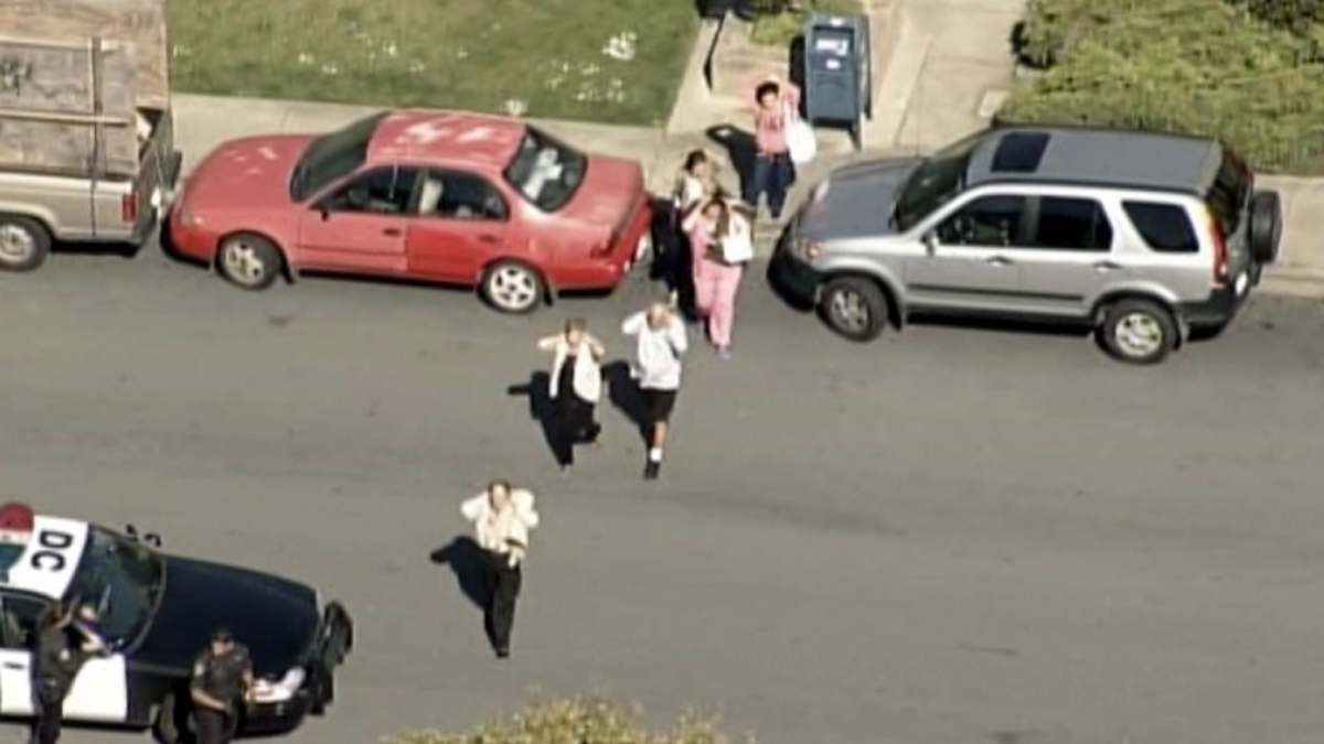 People are seen being led by police away from the medical office building at 1500 Southgate Avenue in Daly City, Wednesday, April 23, 2014.