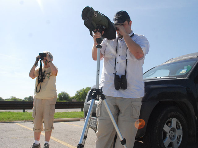 Cook and Thrower use the tools of their trade to spot some birds in the distance at Benbrook Lake.