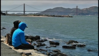 People dangle feet in Bay at Crissy Field