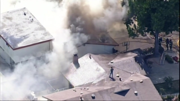 [BAY] Raw video: Homeowner Tries to Douse Roof to Prevent Flames from Spreading