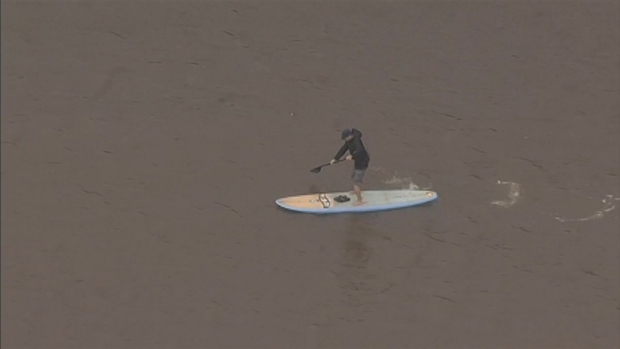 RAW: Man Paddleboards in Flooded Mill Valley