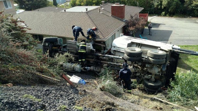 Dump Truck Rolls Over, Slides Into Nearby Home in San Leandro