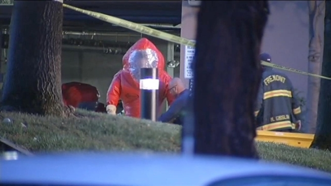 Hazmat crews respond to a Fremont parking garage Wednesday after a woman was found dead in her car. On her windshield, was a sign that said