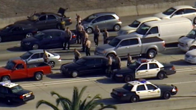 Raw Video: officers searched vehicle-to-vehicle on the northbound 110 Freeway on Friday after a bank robbery in Moreno Valley.