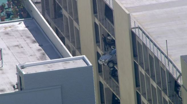 Woman Escapes Car Hanging from Parking Structure
