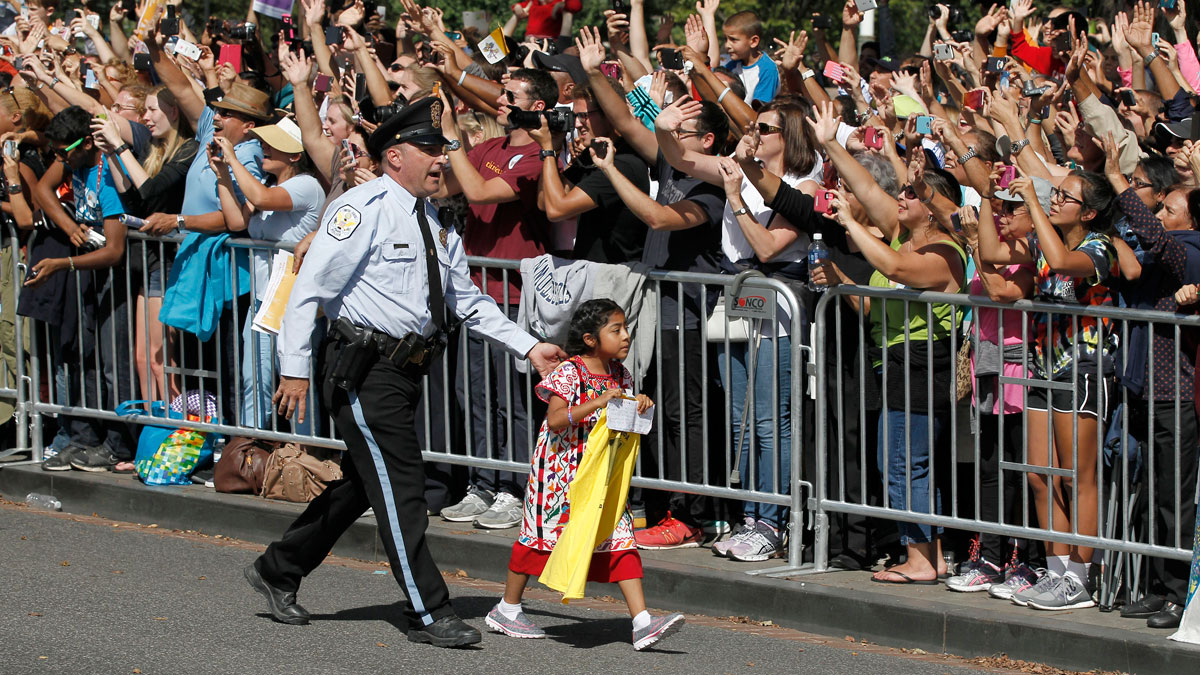 A child is escorted back before Pope Francis called for the child to be brought to him, during a parade in Washington, Sept. 23, 2015.