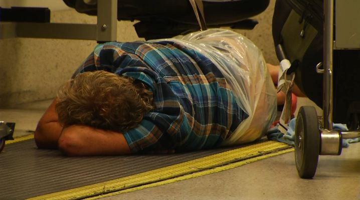 A Norwegian Air Shuttle passenger sleeps on the floor at LAX July 25, 2014. Hundreds of the airline's passengers have been stranded at the airport for days since the Wednesday cancellation of a flight bound for London.